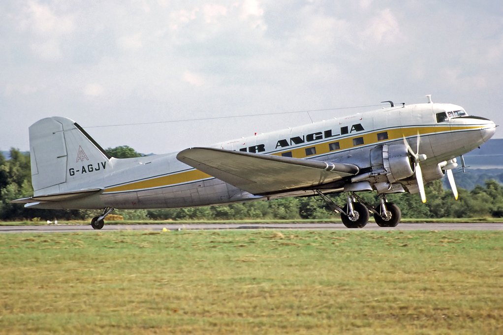 """G AGJV Douglas C47 Dakota 4. Greenham Common July 1973 In service with Air Anglia early 1972. Pictured at Greenham Common during the International Air Tattoo, probably engaged in pleasure flying duties. This aircraft has had the """"Transair Mod"""", which comprised of fitting fibreglass undercarriage doors which were closed by bungee rubbers and fitted against the protruding main wheels and improved the single engine take-off performance. Photo Richard Vandervord."""